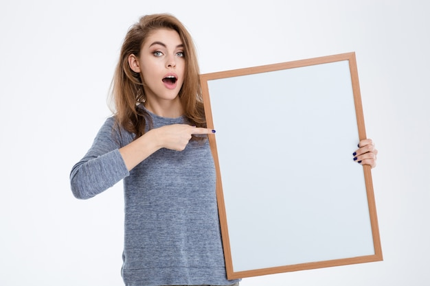 Portrait of a cheerful woman pointing finger on blank board isolated on a white background