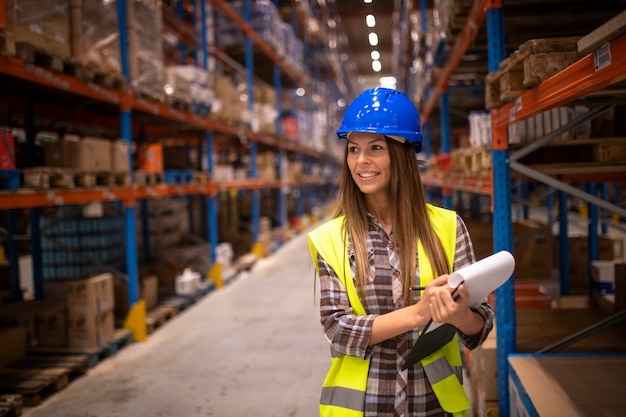 Portrait of cheerful woman in protective uniform checking packages and stock of products in warehouse storage room