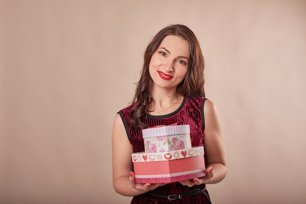 Portrait of cheerful woman in red dress holding gift boxes