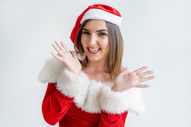 Portrait of cheerful woman in santa claus outfit showing palms