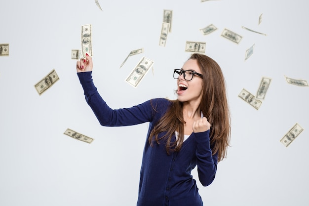 Portrait of a cheerful woman standing under rain of money isolated on a white background