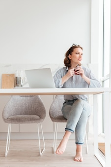 Portrait of cheerful woman in striped shirt and jeans holding cup of tea while sitting at soft chair in the kitchen