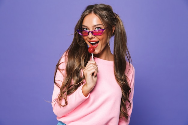 Portrait of a cheerful woman in sunglasses holding lollipop