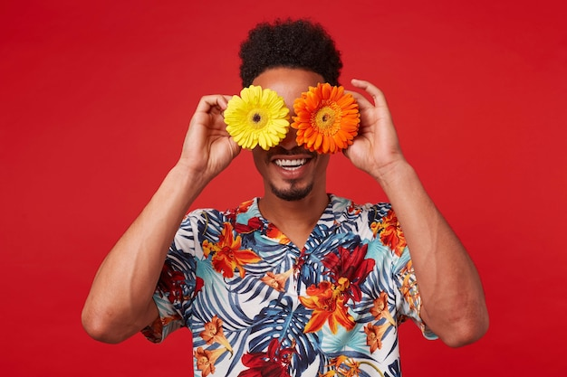 Portrait of cheerful young african american guy, wears in hawaiian shirt, looks at the camera trough flowers with happy expression, stands over red background.