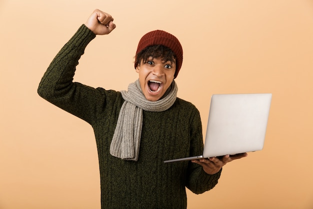 Portrait of a cheerful young african man dressed in autumn clothes isolated over beige wall, holding laptop computer, celebrating