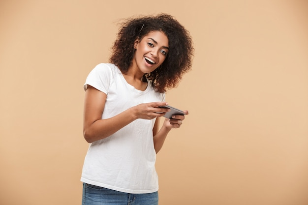 Portrait of a cheerful young african woman playing games