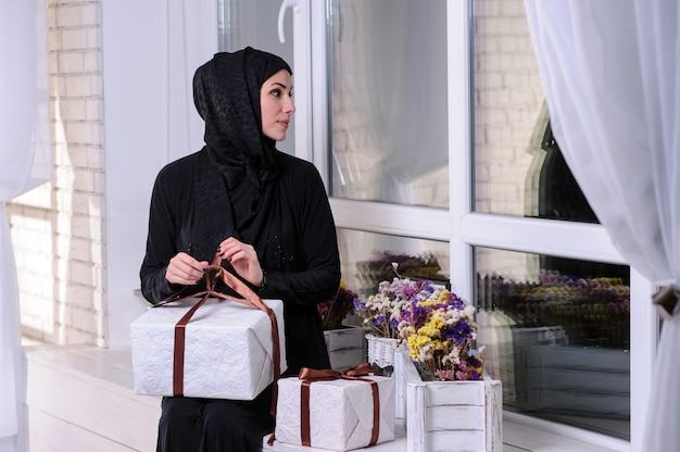 Portrait of a cheerful young arabian woman showing stack of present boxe.