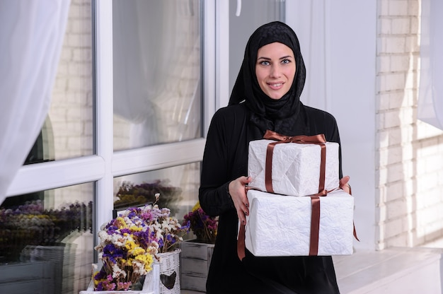Portrait of a cheerful young arabian woman showing stack of present boxes isolated over gray background