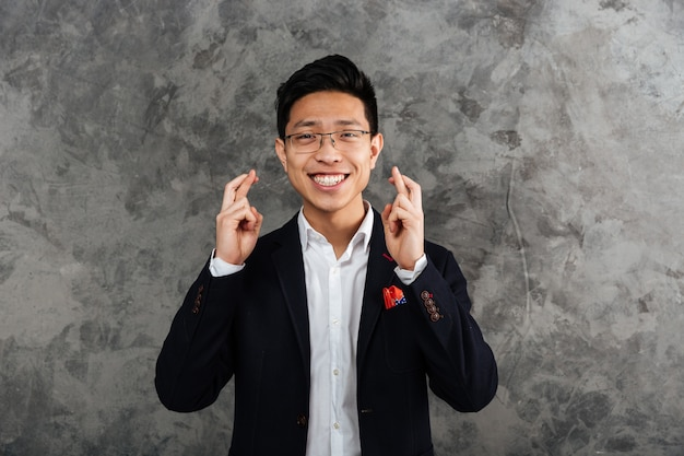 Portrait of a cheerful young asian man dressed in suit