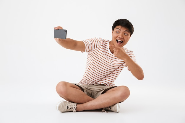 Portrait of a cheerful young asian man taking