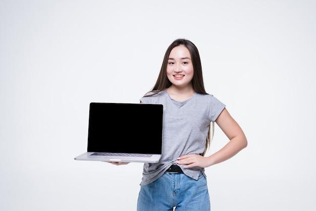 Ritratto di una giovane donna asiatica allegra che indica il dito al computer portatile dello schermo in bianco mentre sedendosi isolato sopra la parete bianca