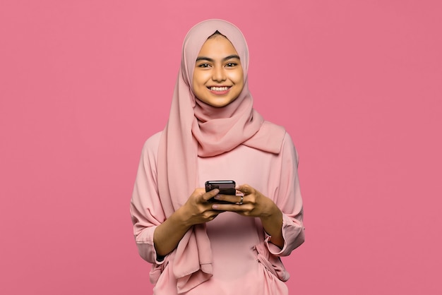 Portrait of cheerful young asian woman using a smartphone with smiling face