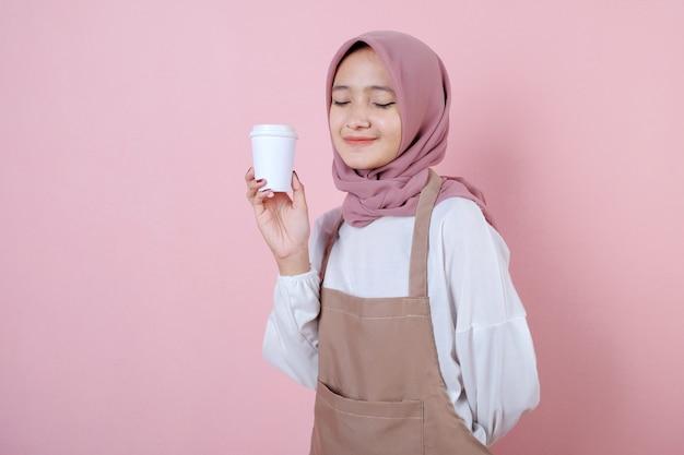 白いカップまたはガラスと陽気な若いアジアの女性の肖像画