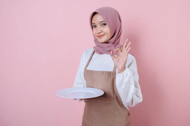 白い皿やプレートと陽気な若いアジアの女性の肖像画