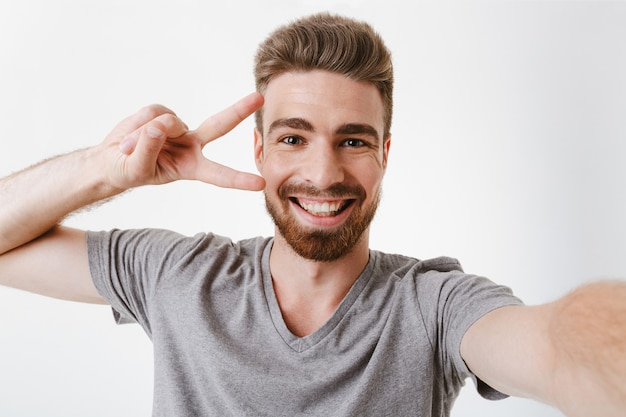 Portrait of a cheerful young bearded man showing peace