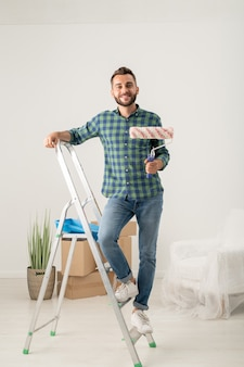 Portrait of cheerful young bearded man standing with paint roller on stepladder in new apartment with moving stuff