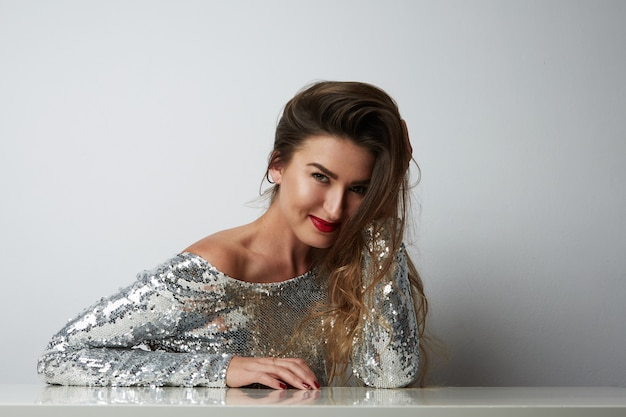 Portrait of cheerful young beatiful woman wearing silver dress and posing at white empty studio.