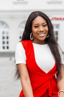 Portrait cheerful young black woman with clean healthy skin with charming smile with beautiful eyes in fashionable red clothes outdoors in city. attractive smiling african girl is relaxes on street.