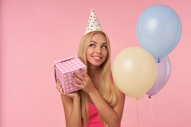 Ritratto di allegra giovane femmina bionda in rosa top e berretto di compleanno in posa in mongolfiere multicolori, guardando da parte felicemente e tenendo presente la casella nelle mani, in piedi su sfondo rosa
