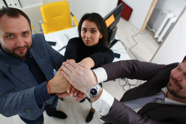Portrait of cheerful young businessmen in office place their hands one over the other