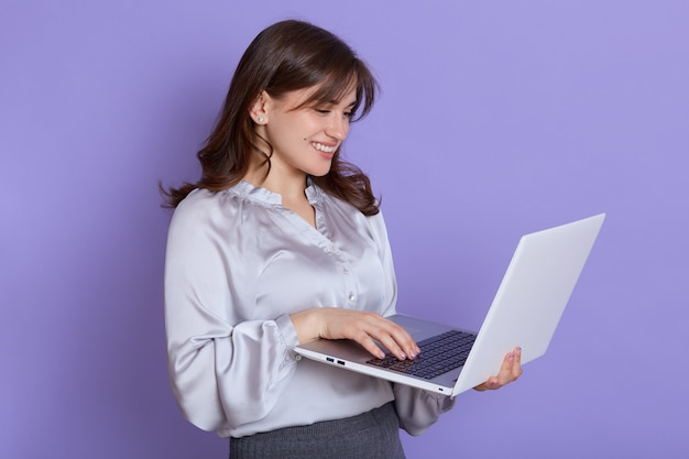 Portrait of cheerful young businesswoman working on laptop and smiling, female with portable computer in hands, being happy, wearing blouse and skirt, attractive lady browsing internet for working.