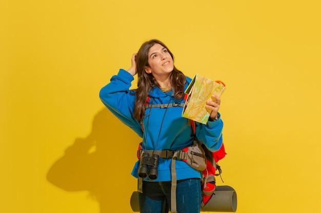 Ritratto di una giovane ragazza turistica caucasica allegra con borsa e binocolo isolato su sfondo giallo studio.