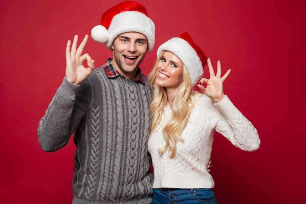 Portrait of a cheerful young couple in christmas hats
