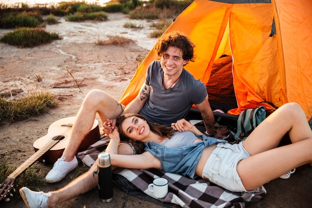 Portrait of cheerful young couple relaxing at the camp tent