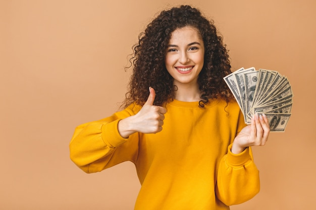 Portrait of a cheerful young curly woman holding money banknotes and celebrating isolated over beige background. thumbs up.