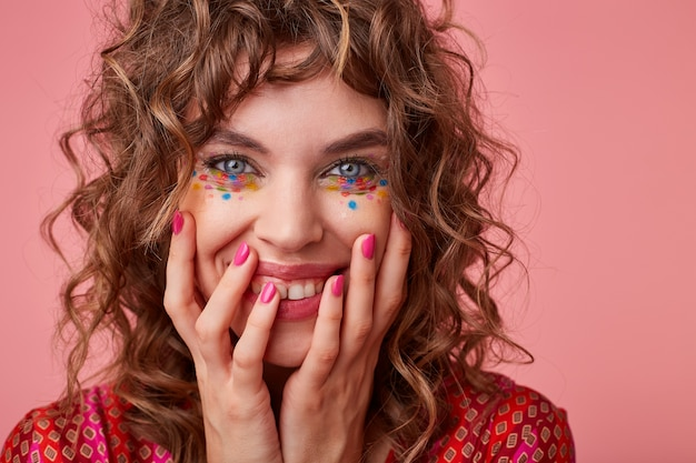 Portrait of cheerful young curly woman with festive makeup holding her face with hands and looking with wide sincere smile, standing