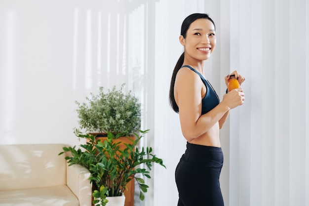 Portrait of cheerful young fit vietnamese woman standing at window in living room and drinking fresh fruit juice
