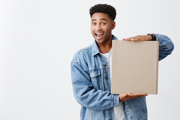 Portrait of cheerful young funny black-skinned man with afro hairstyle in white t-shirt under denim jacket holding cardboard with happy and excited face expression. copy space