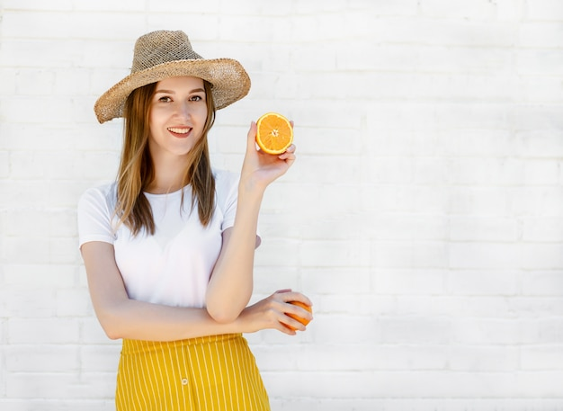 Portrait of a cheerful young girl in hat holding two slices of orange on white wall