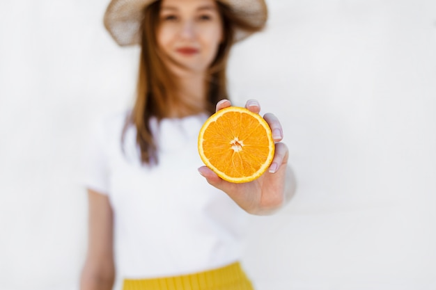 Portrait of a cheerful young girl holding of orange on white wall
