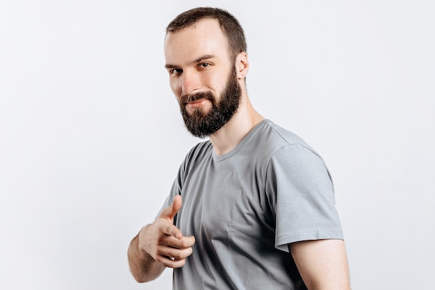 Portrait of cheerful young handsome man smiling looking at camera pointing finger forward on white background with space for advertising mock up