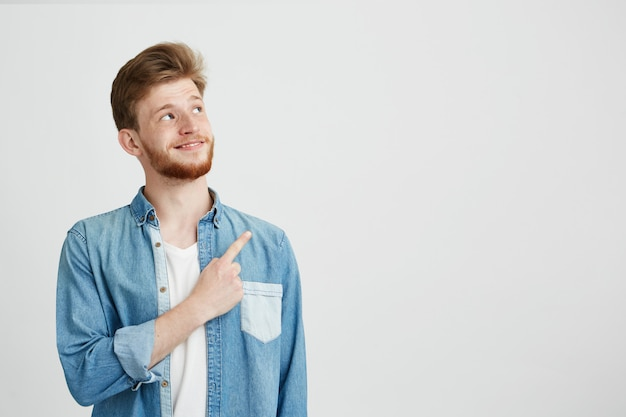 Portrait of cheerful young handsome man smiling pointing finger up.