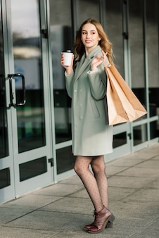 Portrait of a cheerful young lady holding shopping bags outdoor
