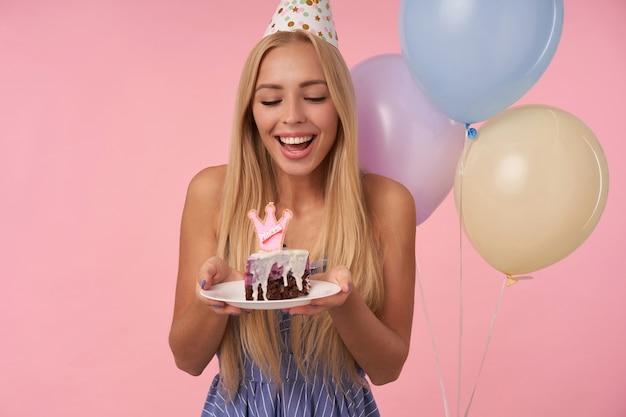 Ritratto di allegro giovane dai capelli lunghi donna che indossa abiti estivi blu che celebrano le vacanze, in posa in mongolfiere multicolori con torta di compleanno, isolate su sfondo rosa