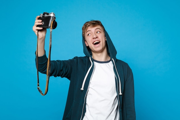 Portrait of cheerful young man in casual clothes doing selfie shot on retro vintage photo camera isolated on blue wall . people sincere emotions, lifestyle concept.
