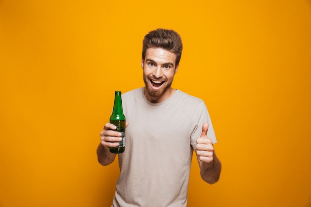 Portrait of a cheerful young man holding beer bottle