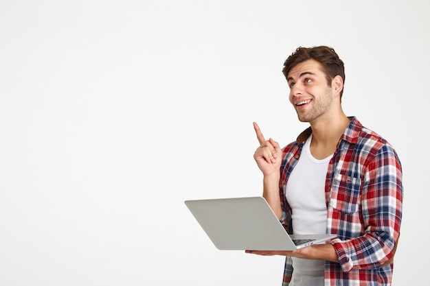 Portrait of a cheerful young man holding laptop computer