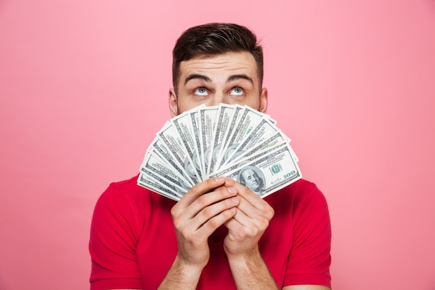 Portrait of a cheerful young man holding money banknotes