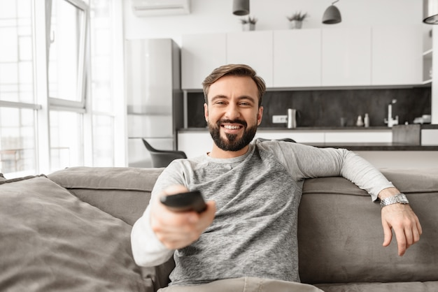 Portrait of a cheerful young man holding tv remote control