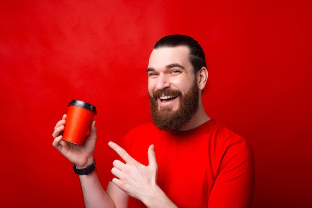 Portrait of cheerful young man smiling and pointing at coffee cup to go over red wall