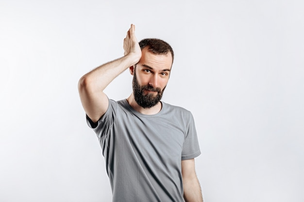Portrait of cheerful young man smiling while looking at camera holding hands out to sides on white background with space for advertising mock up