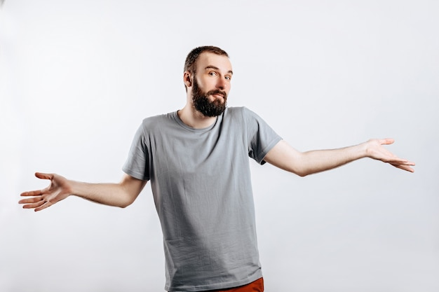 Portrait of a cheerful young man smiling while looking at the camera, throwing up his hands to the sides from ignorance on a white background with a place for advertising mockup