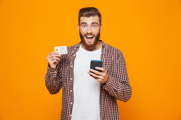 Portrait of a cheerful young man wearing casual clothes holding mobile phone showing plastic credit card