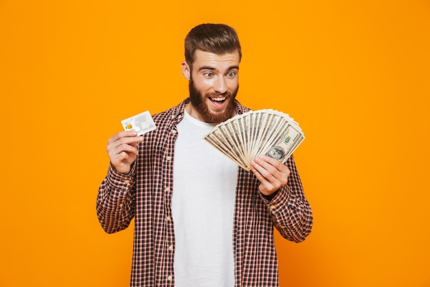 Portrait of a cheerful young man wearing casual clothes holding money banknotes showing plastic credit card