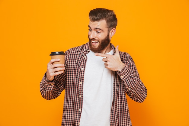 Portrait of a cheerful young man wearing casual clothes holding takeaway coffee giving thumbs up