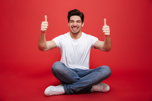 Portrait of a cheerful young man in white t-shirt sitting